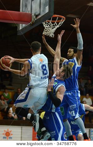 KAPOSVAR, HUNGARY - FEBRUARY 22: Balazs Szoke (in white) in action at a Hungarian Cup basketball game with Kaposvar (white) vs. Fehervar (blue) on February 22, 2012 in Kaposvar, Hungary.