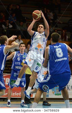 KAPOSVAR, HUNGARY - FEBRUARY 22: Kornel Kiss (in white 6) in action at a Hungarian Cup basketball game with Kaposvar (white) vs. Fehervar (blue) on February 22, 2012 in Kaposvar, Hungary.