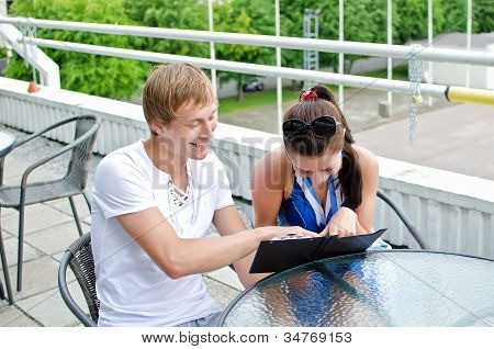 Happy Couple Ordering Food In Summer Cafe