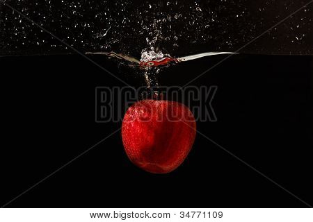 Red apple falling into the water with a splash on a black background