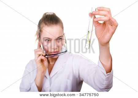 Woman looks to the germinated seed in a test tube