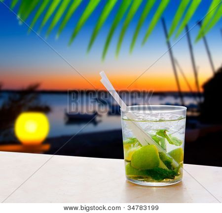 Cocktail Mojito in Balearic island sunset and palm trees [photo-illustration]