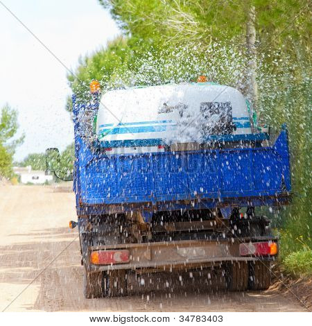 Lorry truck spreading sprinkle water on sand road previous to asphalt works