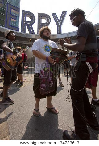 NEW YORK-JULY 11: Occupy Guitarmy protesters play music on drums and guitars before leaving the Staten Island Ferry area during the #99MileMarch from Philly to NYC on July 11, 2012 in New York, NY.