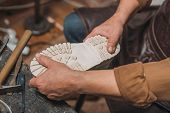 Cropped View Of Shoemaker Fixing Sole To Boot In Workshop poster