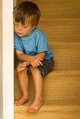 stock photo of child abuse  - Impression of a neglected child sitting on carpeted stairway - JPG