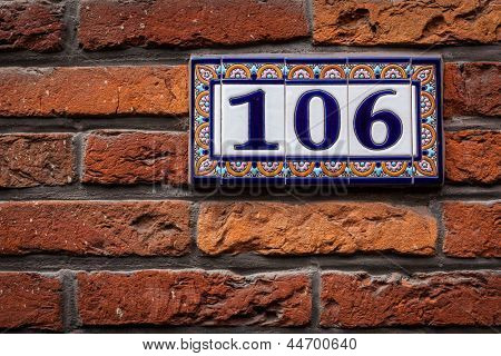 Decorated house number on brick wall in Europe. Bruges (Brugge), Belgium
