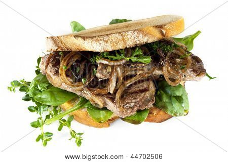 Steak sandwich made with sourdough bread, caramelized onions and fresh herbs, isolated on white.