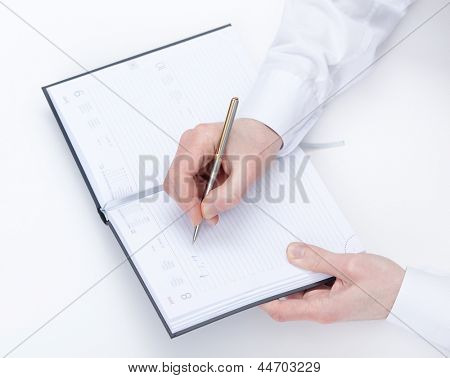 Top view of making notes hand of businessman sitting at the table, isolated on white