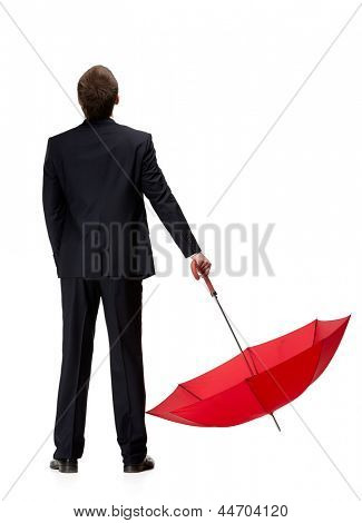 Back view of man in suit holding down opened red umbrella, isolated on white