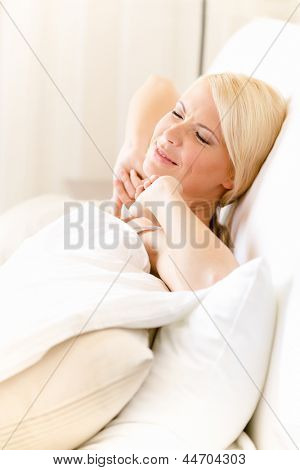 Woman stretches herself lying in bed in the morning at weekend