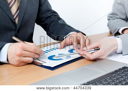 Two business people discuss financial issues sitting at the business table with documents, isolated on white