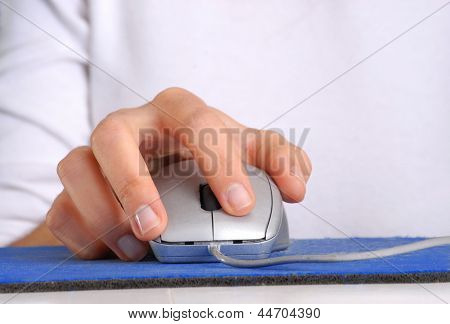 Hand clicking computer mouse.
