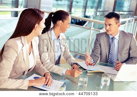 Serious boss looking at his employees while commenting a document at meeting