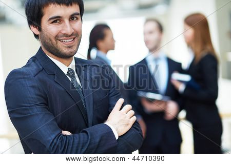 Portrait of friendly male leader looking at camera in working environment