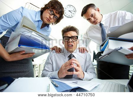 Pleading accountant looking at camera being surrounded by his partners with huge piles of documents