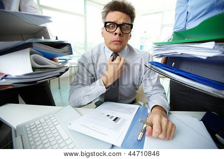 Shocked accountant looking at camera surrounded by huge piles of documents held by his partners
