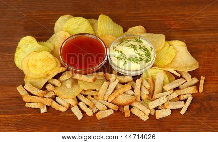Potato chips, crackers and sauce, on wooden background