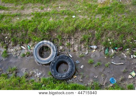 Concept or conceptual unhygienic polluted river,sewage or dirty water and grass with waste,trash and dump background,metaphor to pollution,environment,ecology,contamination,recycle,damage old problem