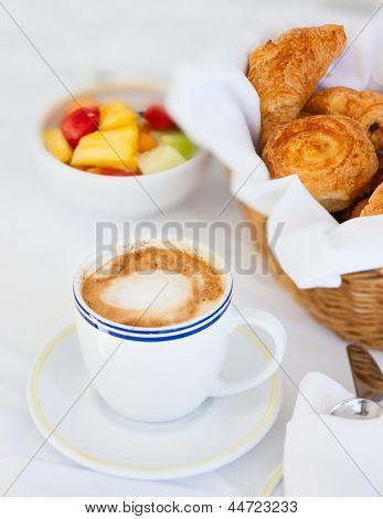 Selection of freshly baked pastry, fruit salad and cappuccino served for breakfast