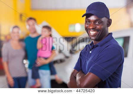 trustworthy african auto mechanic standing in front of family inside garage