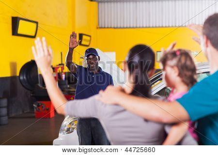 friendly african auto repair shop worker waving good bye to customer