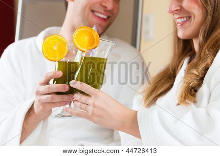 Young couple - man and woman - drinking Chlorophyll-Shake in spa