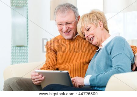Quality of life - two elderly people sitting at home on the couch and writing emails on the tablet computer
