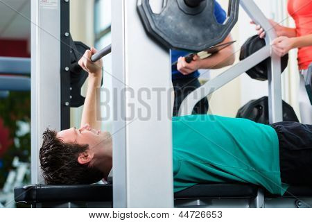 Man with his personal fitness trainer in the gym exercising with dumbbells, he used a barbell on a weight bench