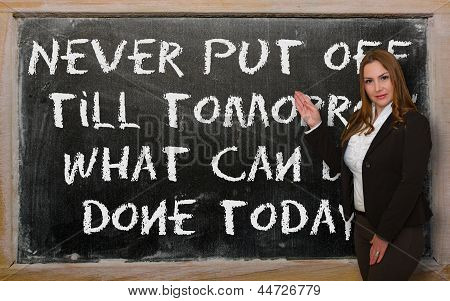 Teacher Showing Never Put Off Till Tomorrow What Can Be Done Today On Blackboard