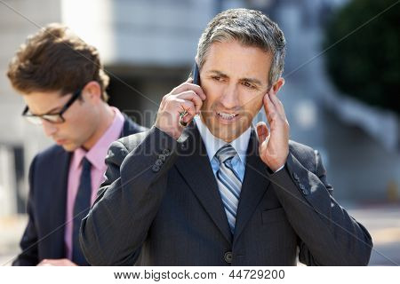 Businessman Speaking On Mobile Phone In Noisy Surroundings