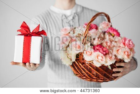 close up of man holding basket full of flowers and gift box.