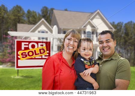Mixed Race Young Family in Front of Sold Home For Sale Real Estate Sign and New House.