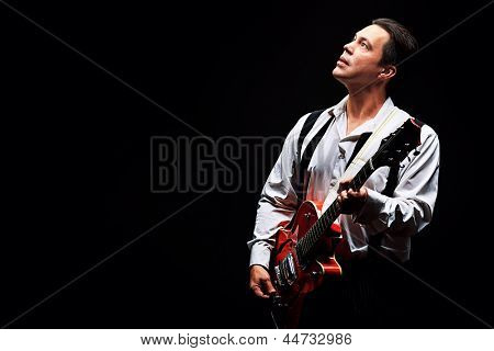 Portrait of a professional artist playing on guitar. Over black background.