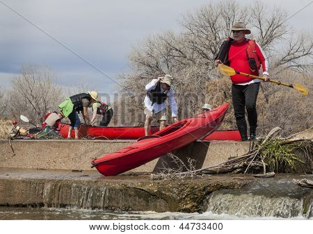 SOUTH PLATTE RIVER, EVANS, COLORADO - APRIL 6: Portaging kayak and canoes over a river diversion dam during Annual All Club Paddle on April 6, 2013. It is a popular season opening paddling trip.