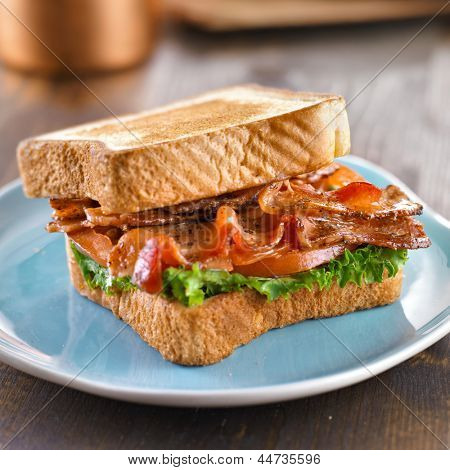 BLT bacon lettuce tomato sandwich with toast off to the side.