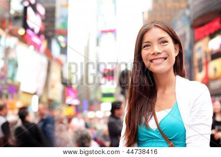 New York City woman as Times Square tourist or young casual woman visiting. Beautiful young happy smiling multicultural Caucasian Asian woman on Manhattan, New York City, New York, USA.