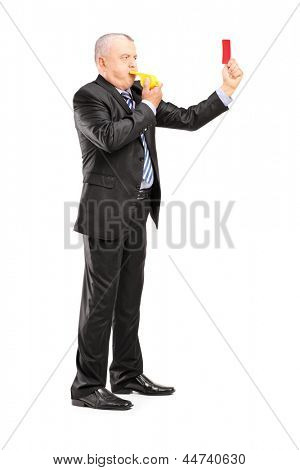 Full length portrait of a mature businessman blowing a whistle and showing a red card, isolated on white background