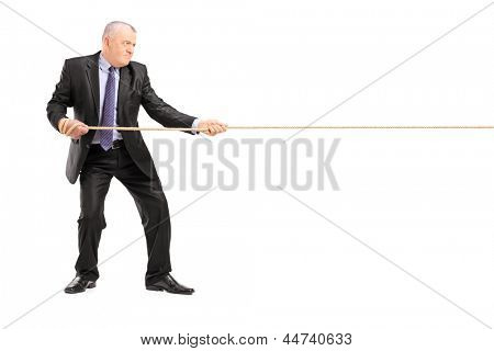 Full length portrait of a mature businessman in suit pulling a rope isolated on white background