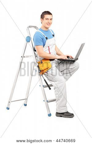 Full length portrait of a handy man with a laptop sitting on a ladder, isolated on white background