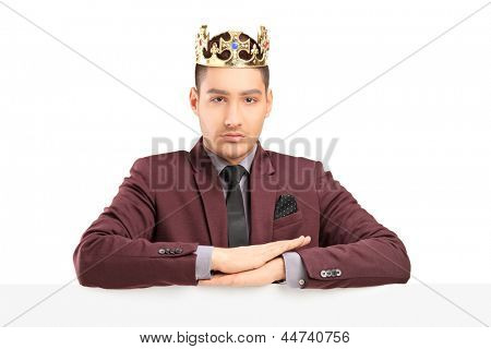 Handsome prince posing on a panel with a diamond crown, isolated on white background