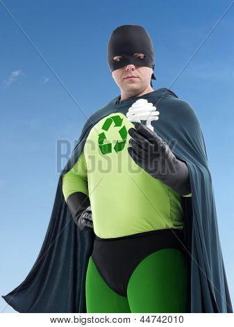 Eco superhero with green recycle arrow symbol on chest holding CFL bulb standing over blue sky - Energy saving concept