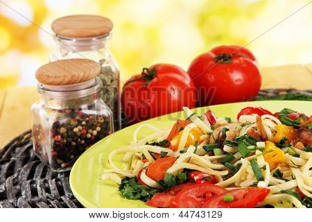 Noodles with vegetables in plates on nature background close-up
