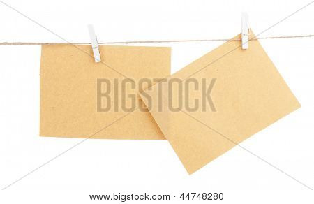 Old sheets of paper hanging on rope isolated on white