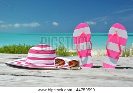 Hat, sunglasses and flip-flops against ocean. Exuma, Bahamas