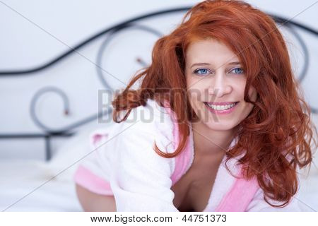 Seductive redhead girl in bed