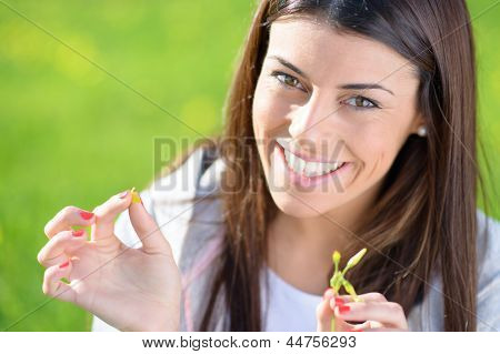 Portrait Of Young Woman Picking Leaf; Outdoors
