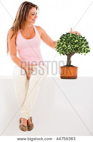 Beautiful woman nurturing a tree - isolated over a white background