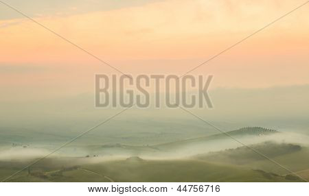 Background image of a very misty morning at dawn in the Tuscan hills at San Quirico d'Orcia