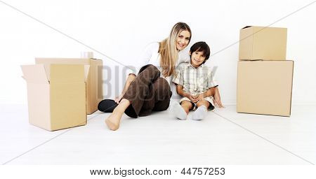 Beautiful smiling woman and little boy sitting alogside cardboard box